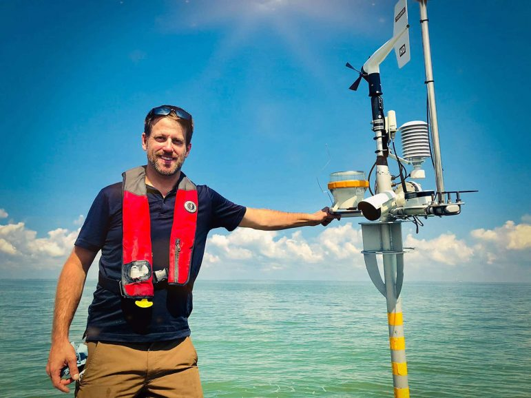 Ed Verhamme of LimnoTech standing with environmental data buoy